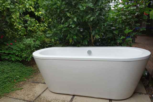 The tub, backed with greenery in a private place on the back patio, is perfect for a hot, relaxing bath.