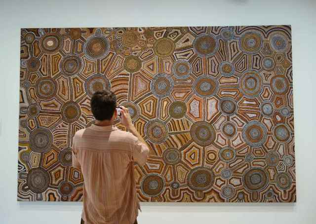 "Our friend, Jamie, also taking a photo of ""Untitled (Jupiter to Tjukula) by Uta Uta Tjangala, 1979."