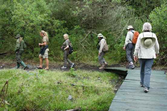 Walking with a park guide in Arusha National Park.