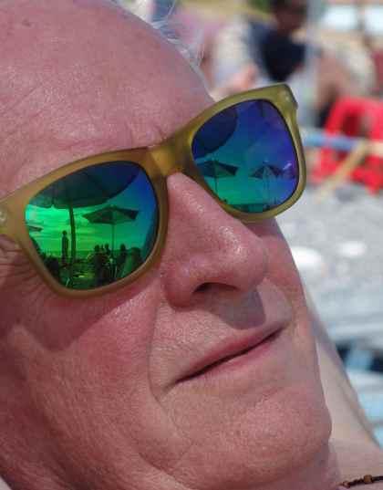 The umbrellas are reflected in Joe's glasses.