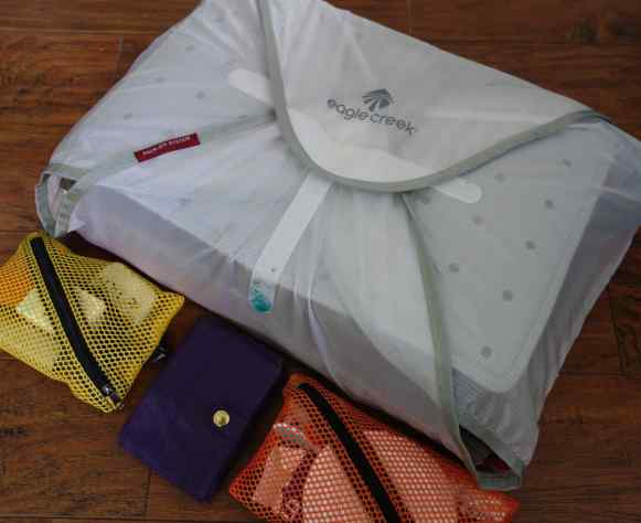 Eagle Creeek pack-it folder holds organizes our shirts, pants and a few sweaters.  Little mesh bags keep the small items from getting lost.  Beth's purple nylon travel wallet gives a sense of scale.