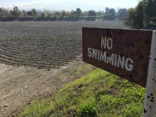 "A nearby official sign read ""Because of the lack of local rainfall and cut backs in water imported from state and federal water projects, groundwater replenishment operations in ponds and creeks have been cut back to conserve water for drinking water treatment plants."""