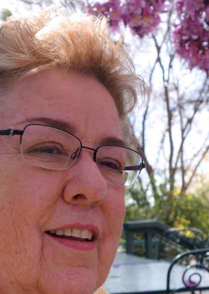 Sue's photo was cropped to emphasize her lips and the flowers – both pink - with her glasses bisecting the image.