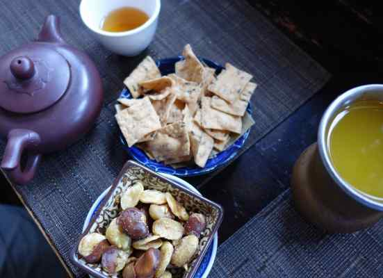 """Joe drank Golden Monkey tea, grown near the Tai Mu Mountains in the Fujian province of China. The tea was described as an """"uplifting, full-bodied brew with honey sweetness…"""" Beth drank mango nectar, and we shared horsebeans (lightly roasted fava beans) and sesame chips."""