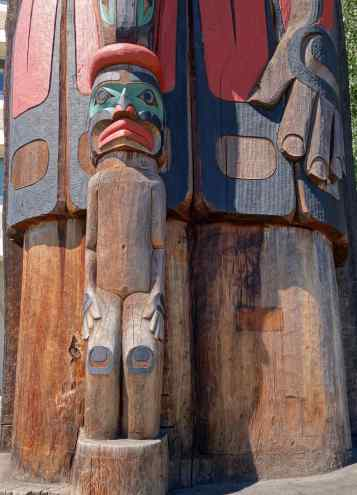 """The Great Chief (represented as a killer whale) whose hand is protectively near the small Man (who represents the members of the artist's tribe) from """"Cedar Man Walking out of the Log"""" Totem by Richard Hunt of the Kwaguilth people"""