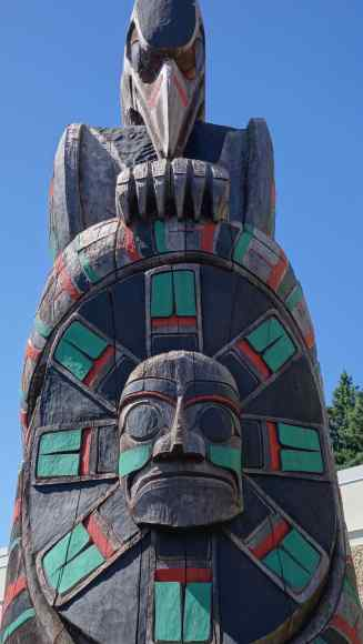 """The Maquinna Sun Mask, carved on feast bowls given to tribes when a fishing and hunting boundaries settlement was agreed, on the """"Peaceful Boundaries"""" Totem by Norman John of Coast Salish heritage"""