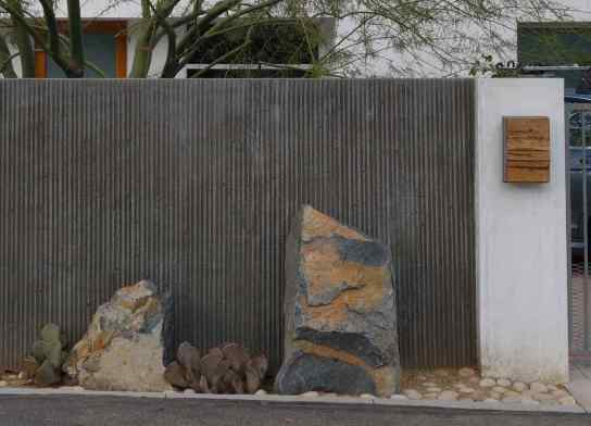 The composition of the rock, cactus, mailbox, and metal wall is well-balanced and beautifully designed.