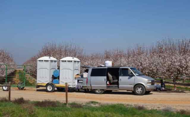 As Beth snapped, snapped, snapped images of the almond trees from our speeding car, the unexpected happened. Who knew the delivery of portable toilets would be so perfectly framed in one of the photos?