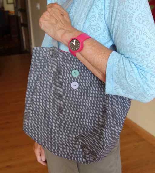 The bag fits snugly under her arm and is super lightweight. The decorative buttons are on the front of the bag so Beth knows just where items are when she reaches in.