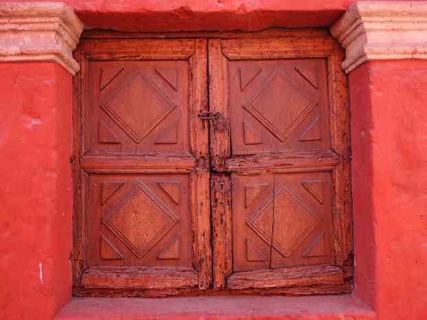 The doors and window shutters are all carved wood. The walls have been maintained in their original colors, vibrant blue and red-orange.