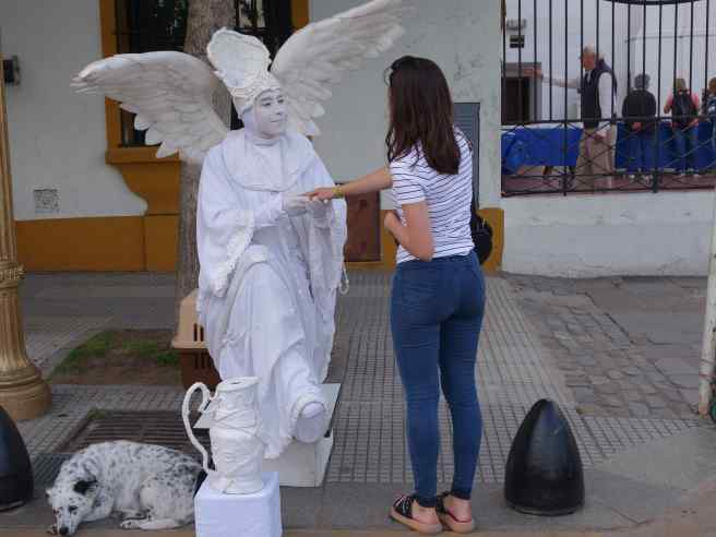 We walked down the street in Buenos Aires and saw a rather unusual scene. Our heads turned as we tried to understand what we were seeing. We finally realized the angel was outside the Recoleta Cemetery and the pedestrian was being thanked silently for dropping a contribution in the angel's pitcher. We pulled out our cameras to capture the scene.